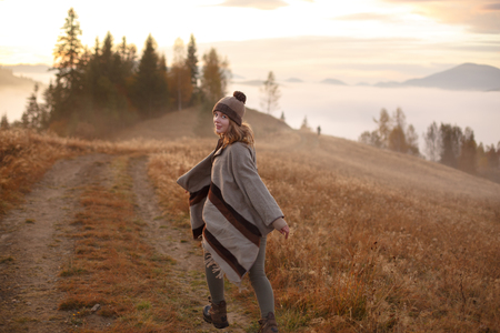 young woman hiking at mountain peak above clouds and fog Hiker girl wrapping in warm poncho outdoor.Early morning.Misty mountain.Young woman in a dress running to the sun in the mountains. Boho style