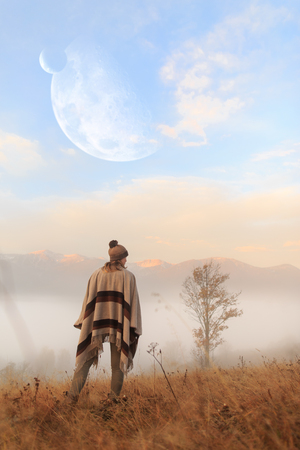 Back view of girl looking at planets. Woman in boho style. Beautiful space scene. Early morning. Misty mountain. Young girl over the clouds in the valley looking at calm autumn sunrise.