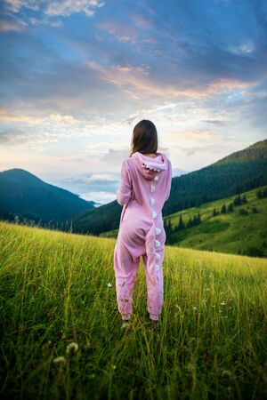 Slim lady in pink Dragon Pajamas in the mountains. Women in pink night-suit. Animal Cosplay Costume. Summer adventure journey in mountain nature outdoors