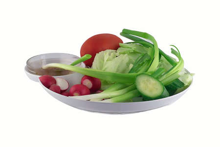 Vegetables tomato,green onion,radishes,lettuce and cucumber on the plate isolated on a white background
