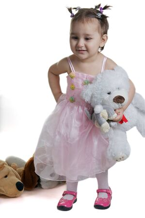 Beautiful and smilling child with toy  white bear isolated against white  photo