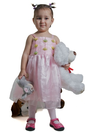 Beautiful and smilling child with toy rabbit and white bear isolated against white  photo