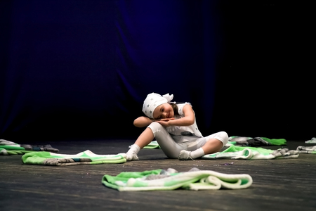 depicts: Dance sleeping - girl on the scene depicts a dream and smiling. Childrens choreography