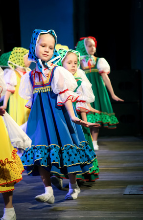 coquetry: Girls in Slavic costumes and scarves on their heads dancing folk dance on stage. Coquetry and modesty Editorial
