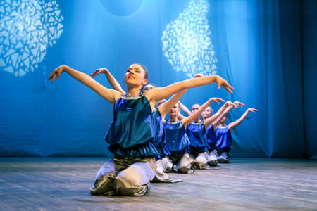 his: Girls dancers depicts the bird and puts his hands up, they smile. Modern choreography, performance Editorial