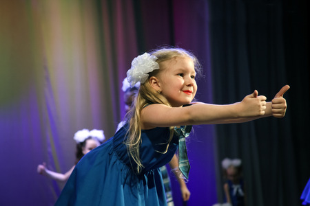children's show: A girl shows a thumbs-up - she was a dancer on the stage. Childrens choreography