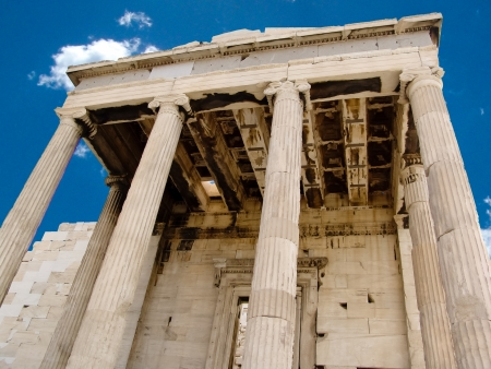 demos: Details of an ancient, ruined Greek portico with columns.