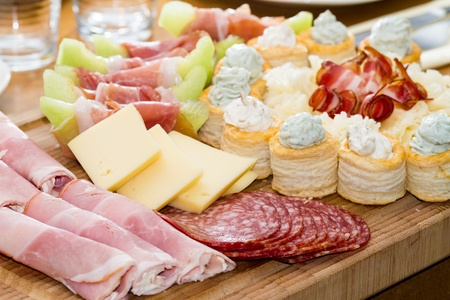 An assortment of appetizers made from sliced meats, cheese, melon and biscuits. photo