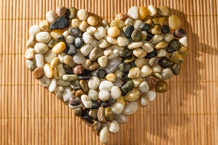 neutrals: Small pebbles or stones in neutral colors shaped like a heart on a bamboo mat.