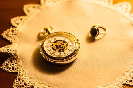 heirlooms: Una vista di un vecchio antico orologio da tasca e un anello d'oro su una fantasia di lino antico centrino. Archivio Fotografico