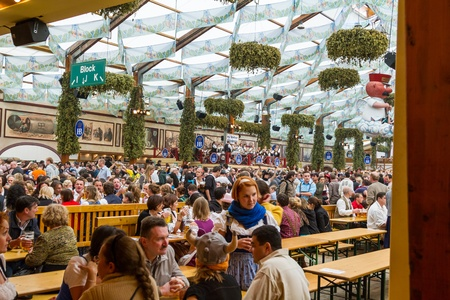 munich: On the traditional Oktoberfest in Munich with thousands people drinking good beer Editorial