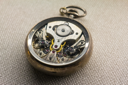 meticulous: Front removed from a pocket watch to show details of the intricate mechanism inside. Stock Photo