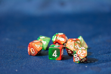risking: A closeup view of a group of colorful, multi-faced dice used for game role playing.  Blue background. Stock Photo