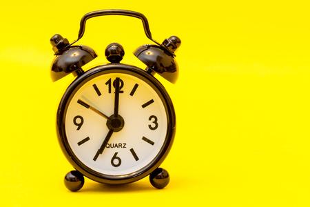 seven o'clock: Black alarm clock on yellow background - seven oclock. Stock Photo