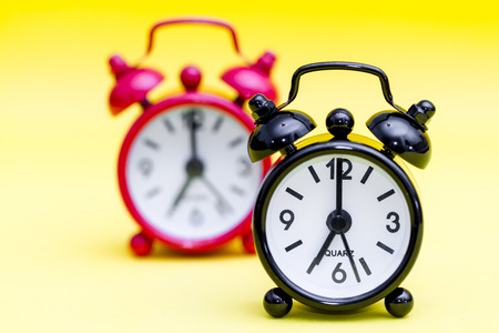 seven o'clock: Two retro alarm clocks on yellow background displaying seven oclock.