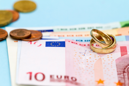 denominational: Two golden wedding rings on stack of Euro money with scattered coins; blue background.