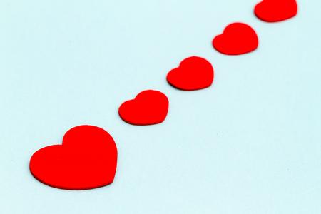 receding: Row of red love hearts receding on light background.