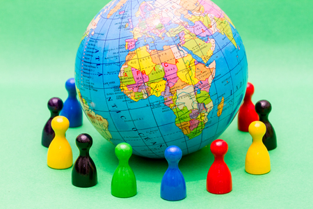 encircling: Colorful people or figures surrounding world globe with map of Africa in foreground. Stock Photo