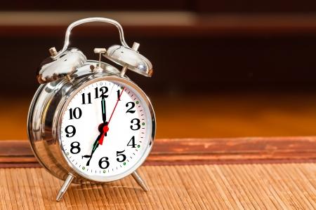 seven o'clock: Retro silver alarm clock showing time as seven oclock.
