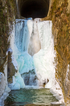 chasm: Closeup of frozen white waterfall in narrow chasm or gorge.