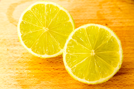 halved  half: Two yellow lemon halves on wooden cutting board background.