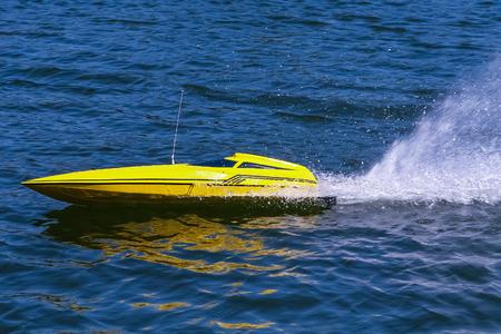 skimming: Amarillo el�ctrica desnatado modelo de barco a trav�s del agua que sale de aerosol en su estela. .