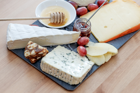 cheeseboard: Cheeseboard: variety of cheese (bluecheese, brie, gouda...) with honey, marmelade and grape. Stock Photo