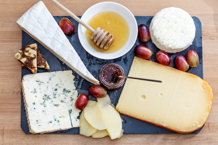 tabla de quesos: Cheeseboard: variety of cheese (bluecheese, brie, gouda...) with honey, marmelade and grape. Foto de archivo