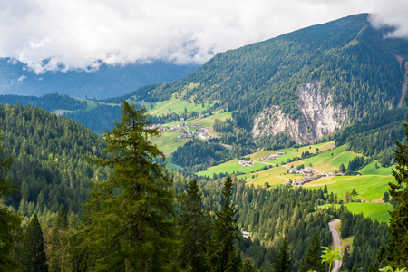 forested: Scenic view of a forested mountainous landscape with green fields of a valley in the background.