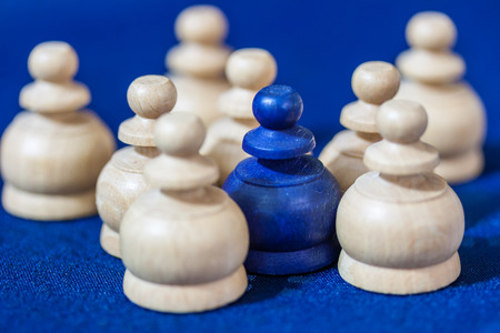 incompatible: Blue wooden chess piece in the center of plain ones on blue background. Stock Photo