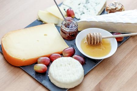 tabla de quesos: Tabla de quesos: variedad de quesos (bluecheese, brie, gouda ...) con miel, mermelada y uva.