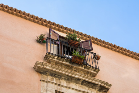 decorative balcony: Old building with door to balcony with safety railing and decorative plants in the city of Syracuse, on the island of Sicily, Italy, blue sky background.