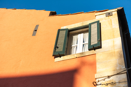 stucco house: Looking up to a green shuttered window in an old stucco house.