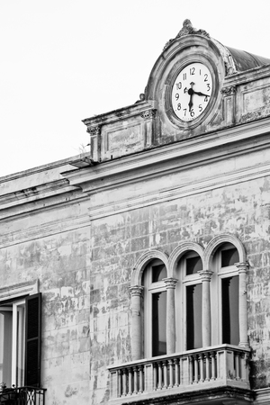 building feature: Detail of historic stone built building in Syracuse, Sicily, with balcony outside three full length windows with columns and above the balcony a large clock in decorative feature. Stock Photo