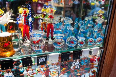 fish exhibition: Souvenir shop in Murano, Venice, with display of colorful glass objects including bowls, clown, and beer glass priced in Euros. Stock Photo
