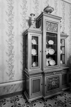 sideboard: Old sideboard with dishes inside room in black and white. Stock Photo