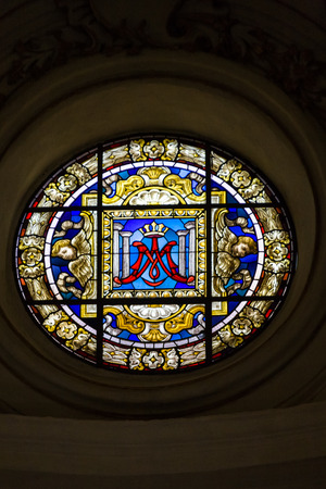 cherubs: Round stained glass window with angels or cherubs and a crown in the center.