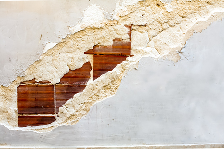 imperfection: Close up of exposed bricks though stucco or dry wall. Stock Photo