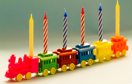 birthday train: Plastic toy train carrying six lit striped birthday candles.
