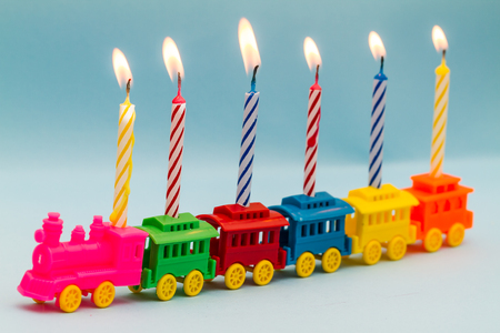 caboose: Plastic toy train carrying six lit striped birthday candles.