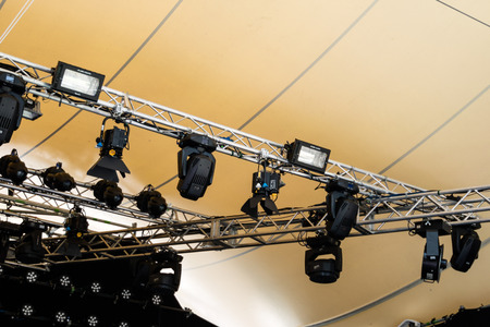 halogen lighting: Various types of stage lights and electrical cords fastened to steel rigging under tent Stock Photo