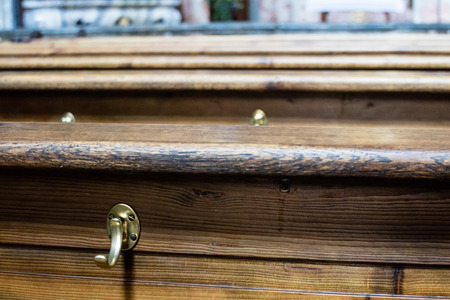 pews: Close up on top edge of old long wooden church pews with brass hooks on the side with copy space Stock Photo