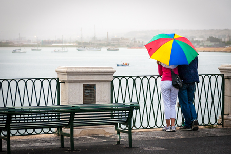sheltering: Couple close together sheltering under one rainbow style umbrella on a bridge or promenade looking out to sea with boats lying at anchor. Stock Photo