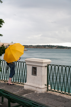 elevated walkway: Girl on elevated walkway, leaning against a railing and holding yellow umbrella while looking out to sea.