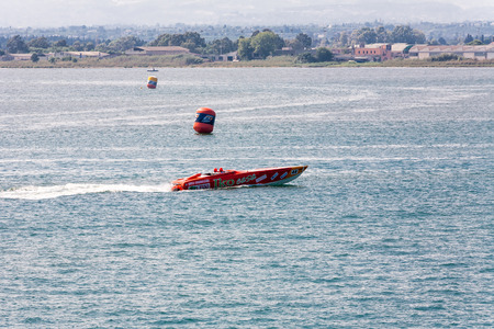 buoys: Thin red speedboat racing along ocean around large buoys with shoreline in background Editorial