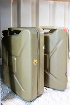 corrugated steel: Pair of drab green metal gas tanks standing upright in shed with white corrugated steel floor beneath them