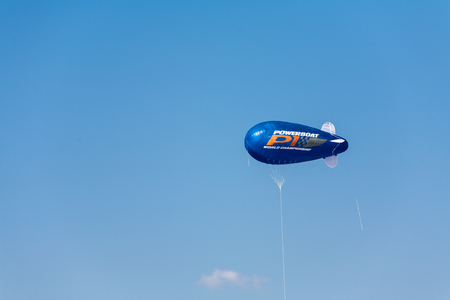 blimp: Single bullet shaped blimp in mid air over blue sky with copy space surrounding it