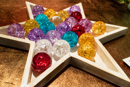 translucent red: Six pointed star shaped wooden container holding various translucent red, white, purple, blue and yellow balls