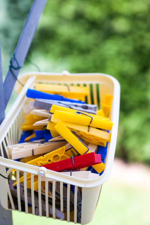 clothes pins: Close up on little basket of yellow, blue and white plastic clothes pins with outdoor foliage background