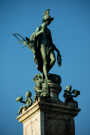 diana: Green copper statue of Goddess Diana on pedestal in Munich Germany with blue sky background